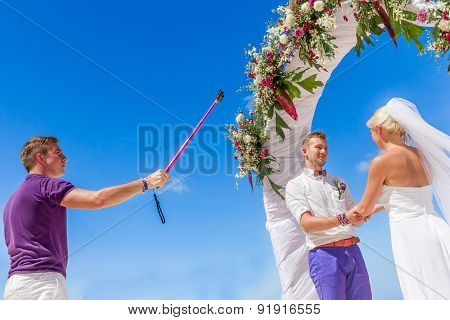 bride, groom and guests enjoying beach wedding in tropics, taking selfie photo on wedding arch, setup background