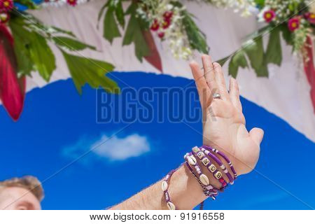 groom's hand with wedding ring on wedding arch, venue background, beach wedding
