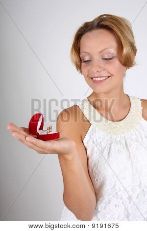 Beautiful Woman Holding Wedding Rings In Red Box