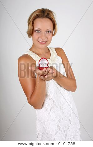 Bride Holding Wedding Rings In Red Box. Focus On Rings
