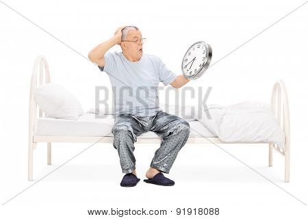 Shocked senior man in pajamas sitting on a bed and holding a big wall clock isolated on white background