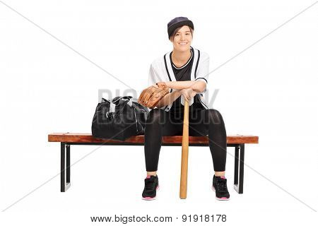 Female baseball player sitting on a bench and looking at the camera isolated on white background