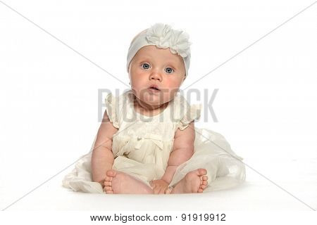baby girl child sitting down on white blanket white dress fashion portrait face studio shot isolated on white caucasian looking at camera