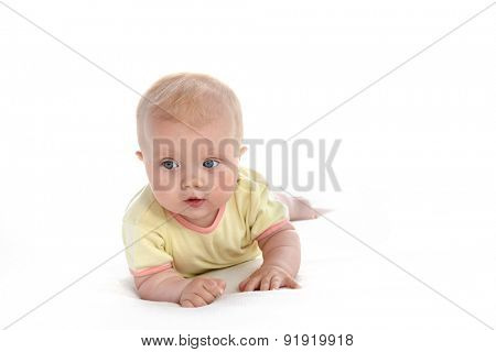 baby girl child lying down on white blanket  portrait face studio shot isolated on white caucasian yellow clothing