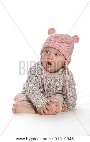 baby girl child sitting down on white blanket  pink fashion portrait face studio shot isolated on white caucasian  hat warm clothing
