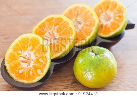 Slice Of Fresh Orange In Wooden Tray