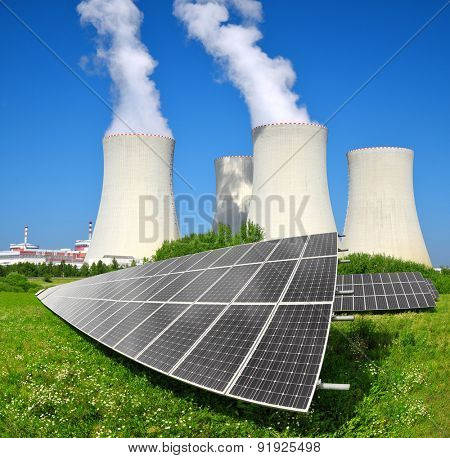 Solar energy panels before a nuclear power plant