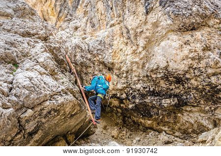 Woman climbing on metal ladder in via ferrata