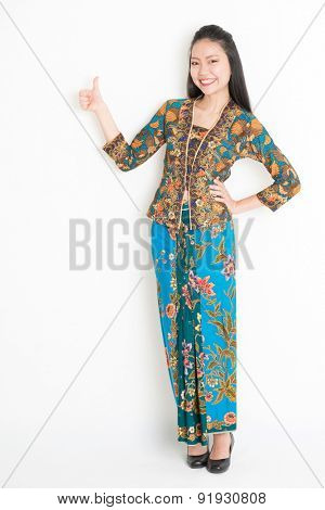 Full body portrait of Southeast Asian woman in batik dress giving thumb up, standing on plain background.