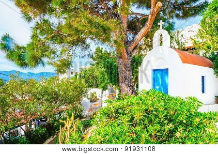 Small white Greek church with blue doors, Greece
