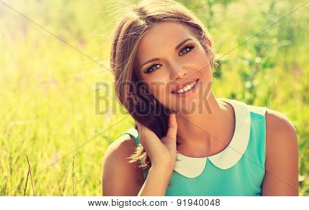Beautiful young girl with a smile lying on the field on the grass