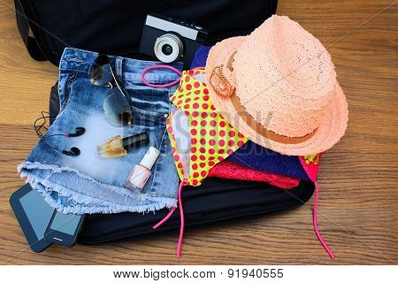 Open the suitcase with tourist things: women's hat, swimsuit, camera, denim shorts, dresses,