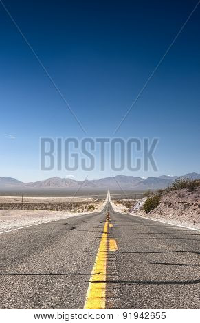 Long Distant Highway Under The Sun Across Death Valley National Park