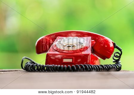 Red phone on wooden deck