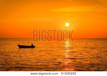 Sea Sunset With A Fishermans Boat Silhouette.
