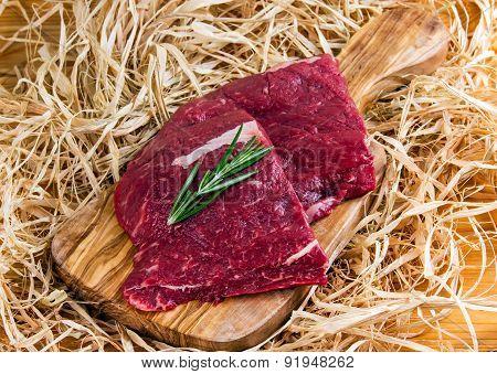 British Beef Flat Iron steak on cutting board and straw, onion
