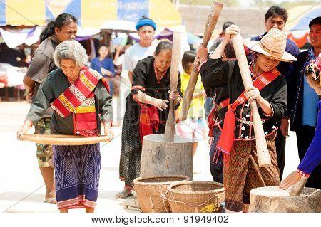 Phutai Minority Woman Pounding and winnowing Rice.