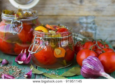 Open glass jar of tasty canned tomatoes
