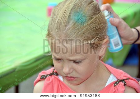 young girl getting hair spray painted