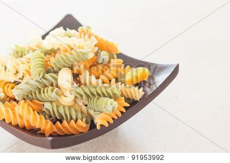 Raw Fusilli Pasta On Wooden Tray