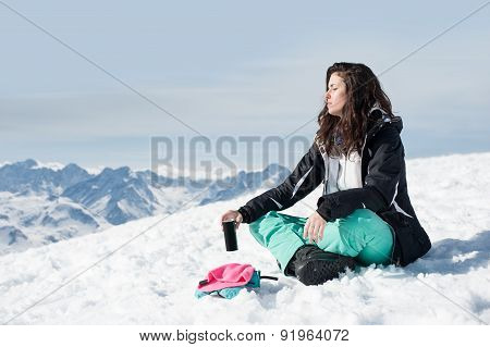 Women at mountains in winter sits on snow