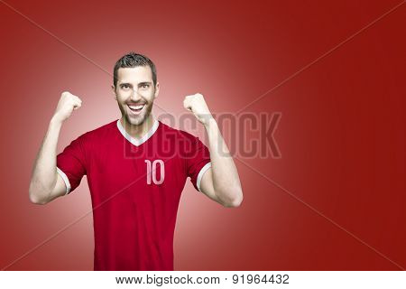 Soccer player on red uniform on red background