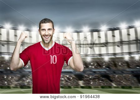 Soccer player on red uniform in the stadium