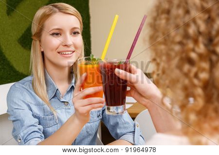 Two women clinking glasses with cocktails in cafe