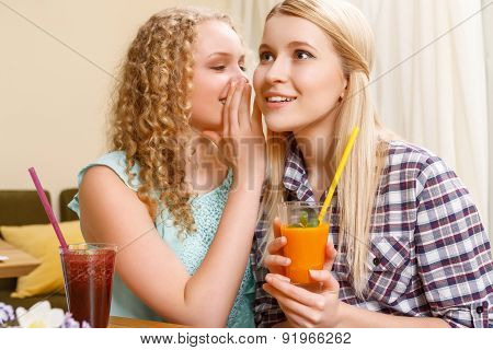 Girl telling secrets to her friend in cafe