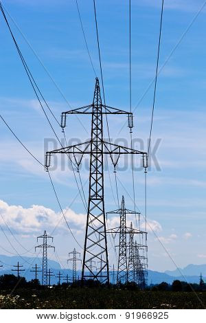 a high-voltage pylons for electricity against a blue sky.