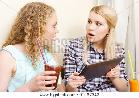 Two amazed girls with tablet in cafe