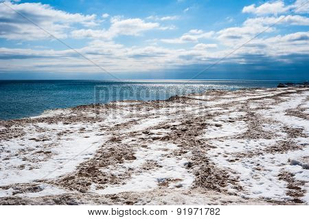 Dirty Ice Field Near Water Under Partly Cloudy Blue Sky.