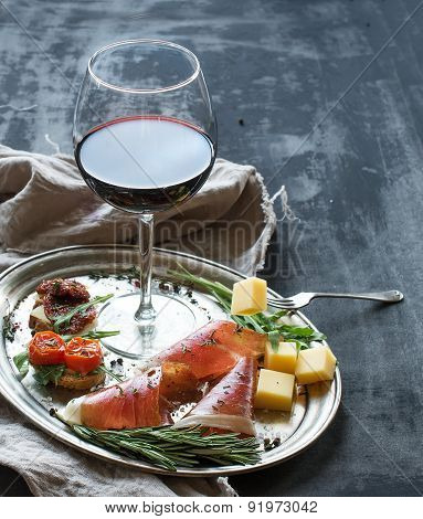 Wine appetizer set. Glass of red wine, vintage dinnerware, brushetta with cherry, dried tomatoes, ar
