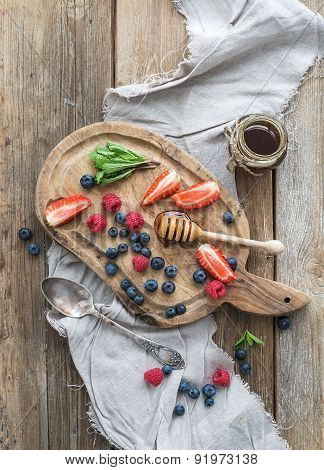 Blueberries, raspberries, strawberries, honey and fresh mint onver  rustic chopping board over wood