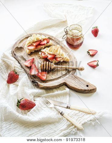 Freshly baked croissants with strawberries, mascarpone and honey on rustic wooden board over white b