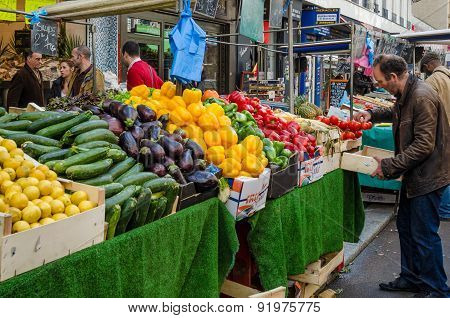 Man shops for tomatoes at a street market in Paris, France