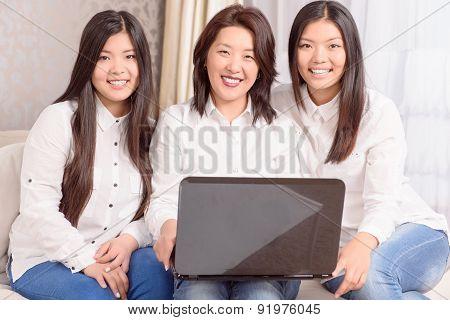 Nice Asian girls sitting at laptop