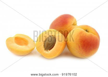 fresh colorful apricots and a cut one on a white background