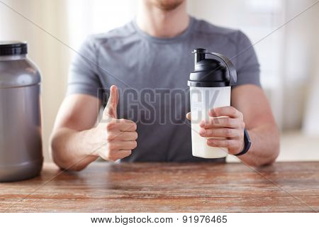 sport, fitness, healthy lifestyle and people concept - close up of man in fitness bracelet with protein shake bottle showing thumbs up