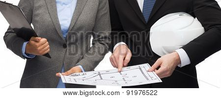 business, architecture and development concept - businesswoman and businessman with clipboard and white helmet pointing finger to blueprint