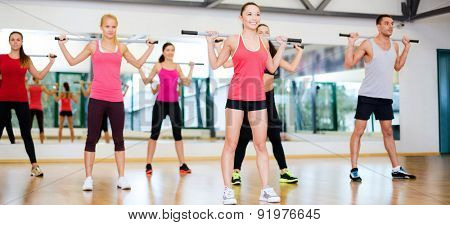 fitness, sport, training, gym and lifestyle concept - group of smiling people working out with barbells in the gym