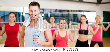 fitness, sport, training, gym and lifestyle concept - smiling trainer in front of group of people working out with barbells in the gym