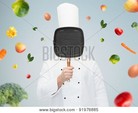 cooking, profession and people concept - male chef cook covering face or hiding behind grill pan over gray background with falling vegetables