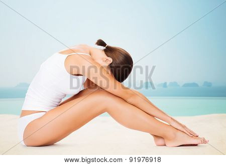 people, beauty, spa, yoga and fitness concept - beautiful woman in cotton underwear over infinity edge pool background