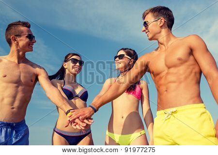 friendship, sea, holidays, gesture and people concept - group of smiling friends wearing swimwear and sunglasses putting hands on top of each other outdoors