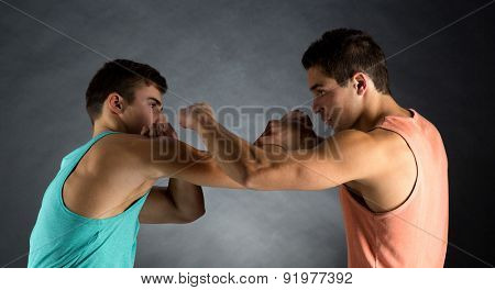 sport, competition, strength and people concept - young men wrestling