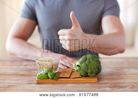 healthy eating, diet, gesture and people concept - close up of male hands showing thumbs up with food rich in fiber