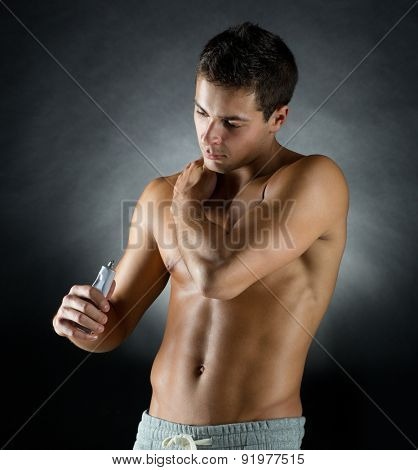 sport, bodybuilding, medicine and people concept - young man standing over black background and applying pain relief gel on his shoulder