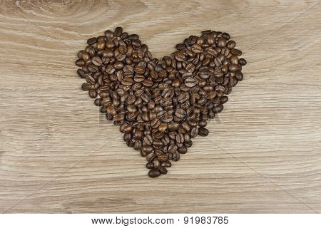 coffee beans in the shape of a human heart on a wooden background