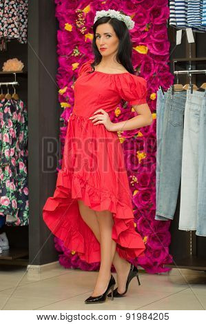 the girl in a red dress in a clothing store